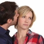 man trying to kiss uninterested wife
